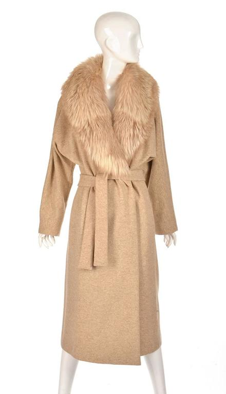 This romantic gold, cream, and fox coat was designed by Bill Blass. The coat is composed of wool accented with a fox fur collar. The coat has a loose, airy silhouette with an adjustable belt. This coat is an elegant classic.  It is in lovely