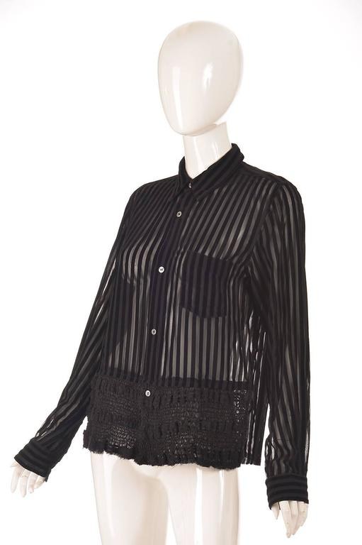 This edgy sheer and velvet striped shirt was designed by Junya Watanabe of Comme des Garcons fame. The blouse has a front left breast pocket, a delicately sheared front hem, and is accented by five mother of pearl buttons going down the front of