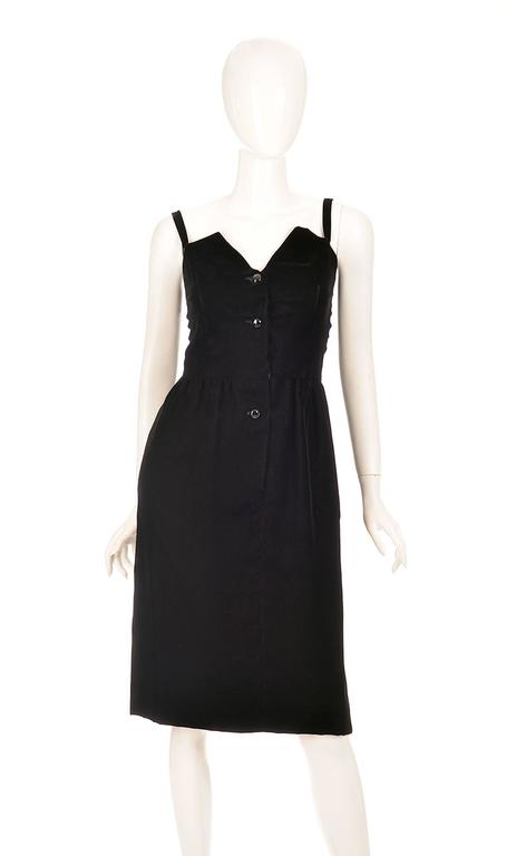 A 1970's Givenchy chic, black, velvet dress made of Viscos and Cupro. The dress features an angular geometric sweetheart neckline with spaghetti straps, buttoned up with polished geometric radial cut black buttons. This dress is knee length, and was