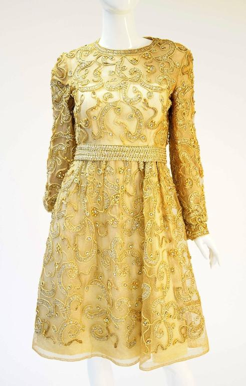 Gorgeous 1960s dress by Malcolm Starr. This gorgeous cocktail dress is knee length, with long, cuffed sleeves, and jewel neckline. The dress features a delicate abstract floral design in gold embroidered passementerie, with rhinestone, sequin, and