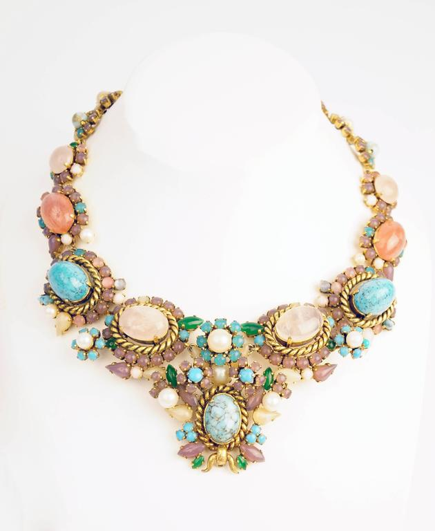 Stunning necklace by Christian Dior, showcasing faux turquoise and rose quartz cabochons surrounded by an elegant and playful assemblage of round and marquise-cut cabochons in purple, pink, green, and pearly white. This necklace of substantial