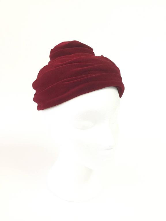 This absolutely gorgeous toque cap by Miss Sally Victor New York is composed of multiple undulating folds of red velvet. The toque cap sits delicately on top of the wearers head and features a notch in the back as both a design element and as a