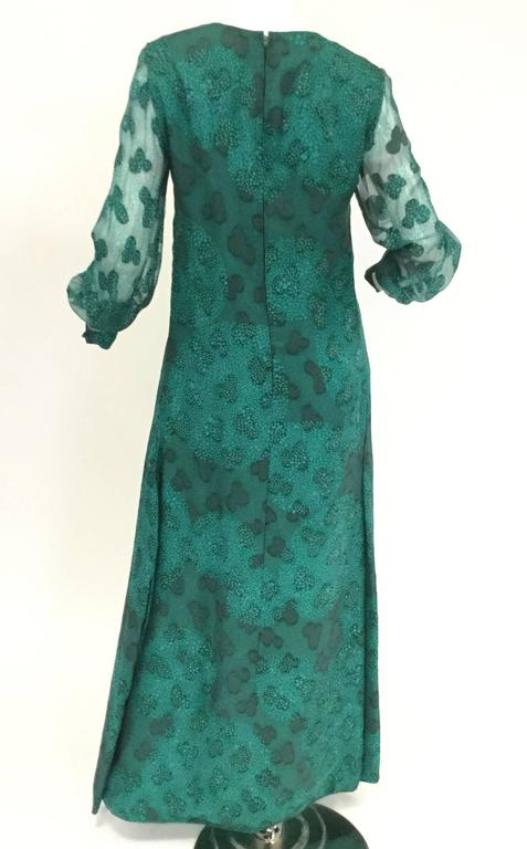 This beautiful and fun  dress by Esther Wolf is absolutely fantastic! This maxi dress has long, sheer, voluminous, cuffed sheer bishop sleeves and a jewel neckline. The dress features a three-leaf clover and speckled dot composite overlay pattern
