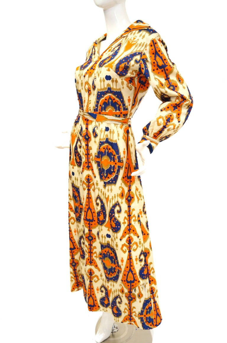You've found it: the perfect breezy dress for a summer soiree. This 1970s calf - length dress features an A - line skirt, an exaggerated wing collar, voluminous cuffed sleeves, and a cinched waist with ribbon belt. The tan, cream, orange, and blue,