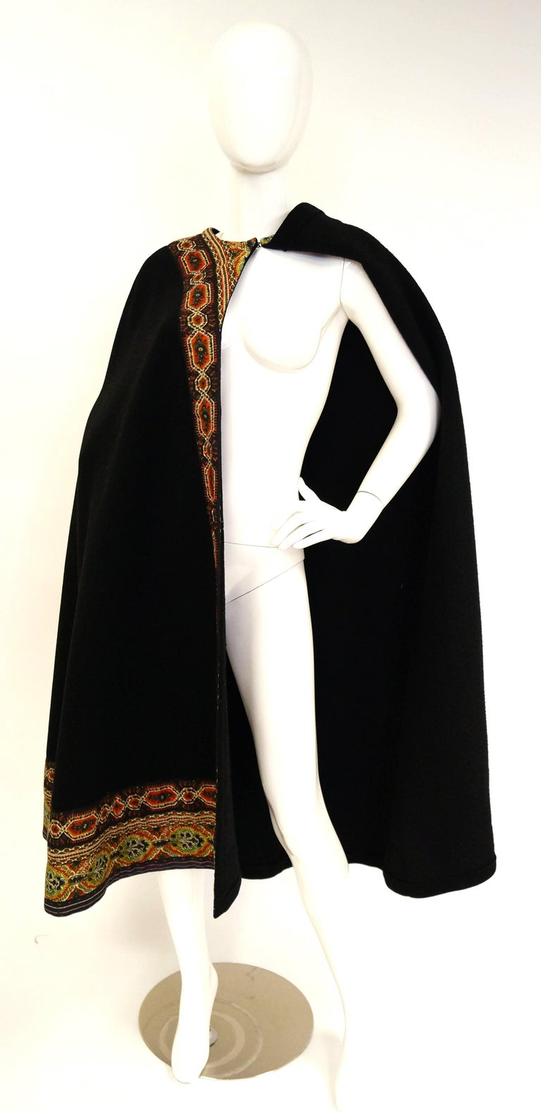 This mid century calf - length wool cloak by Oscar de La Renta is an absolute delight! The cloak is made of soft, thick black wool, and features a bright and colorful bohemian trim. The floral and geometric trim extends around the collar and down