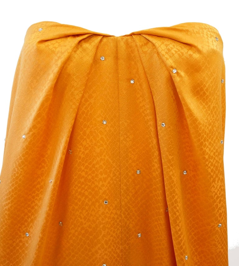 This floor - length dress by Holly's Harp is fantastic!!!!  The dress is composed of tangerine orange silk in a snake print, thoroughly peppered with rhinestones. The dress is midway between a shift and a trapeze dress, and features a sweetheart