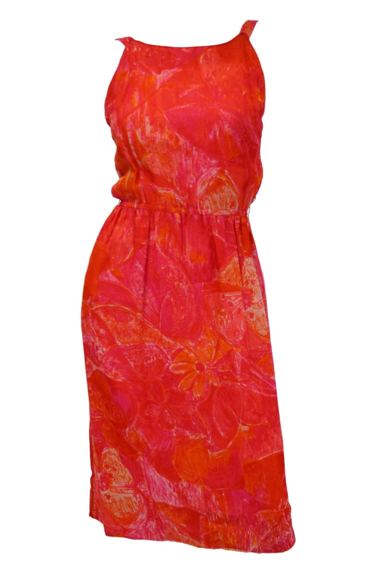 Although the cape on this 1960s red and pink floral print evening dress by Pierre Cardin is too small to let you fly into the room, you can at least smoothly glide in, knowing all eyes are on you. The knee-length dress features a broad scoop neck