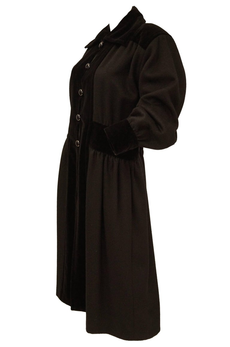 This 1970s YSL coat is soft and supple but with the structure and severe sartorial sophistication one expects from Yves Saint Laurent. The coat consists primarily of warm-toned black wool in a princess cut, with a pinched, gathered waist, cuffed