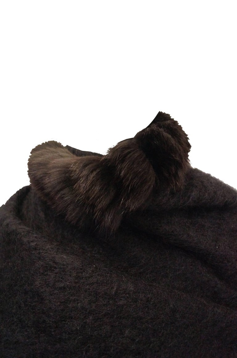 This shawl by Yves Saint Laurent is made of a plush loose knit wool and features long tufts of espresso brown fox fur edging as well as glossy button details. The triangular shawl is large enough to fully wrap around the shoulders and neck, and can
