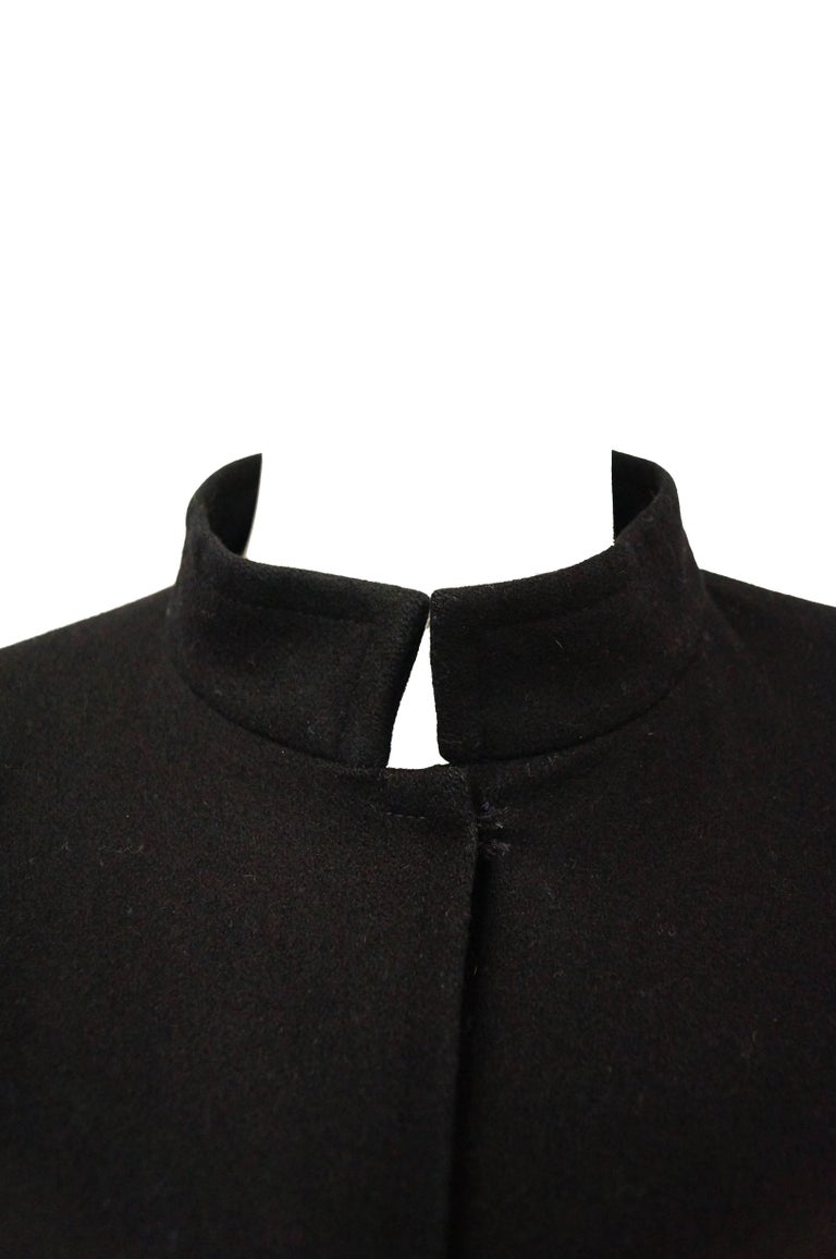 This iconic black wool Yves Saint Laurent cape is mid-calf length and features snaps for closure on the neck. The cape consists of a generous amount of solid black couture raised twill weaved wool, allowing it to slowly and softly billow with