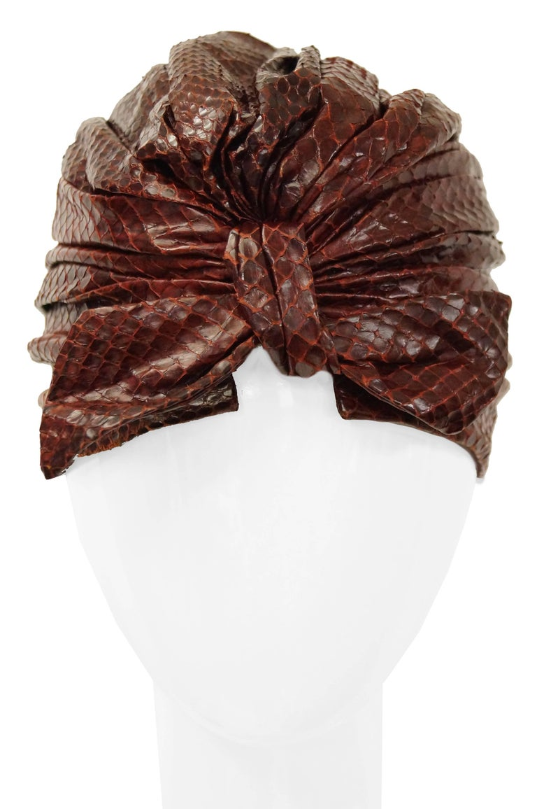 "Absolutely gorgeous mid century sienna brown snakeskin turban ""custom made"" by the Neiman Marcus department store. The turban is made of ruched snakeskin and gathers in a bow at the back. The piece is rather versatile and can be worn"