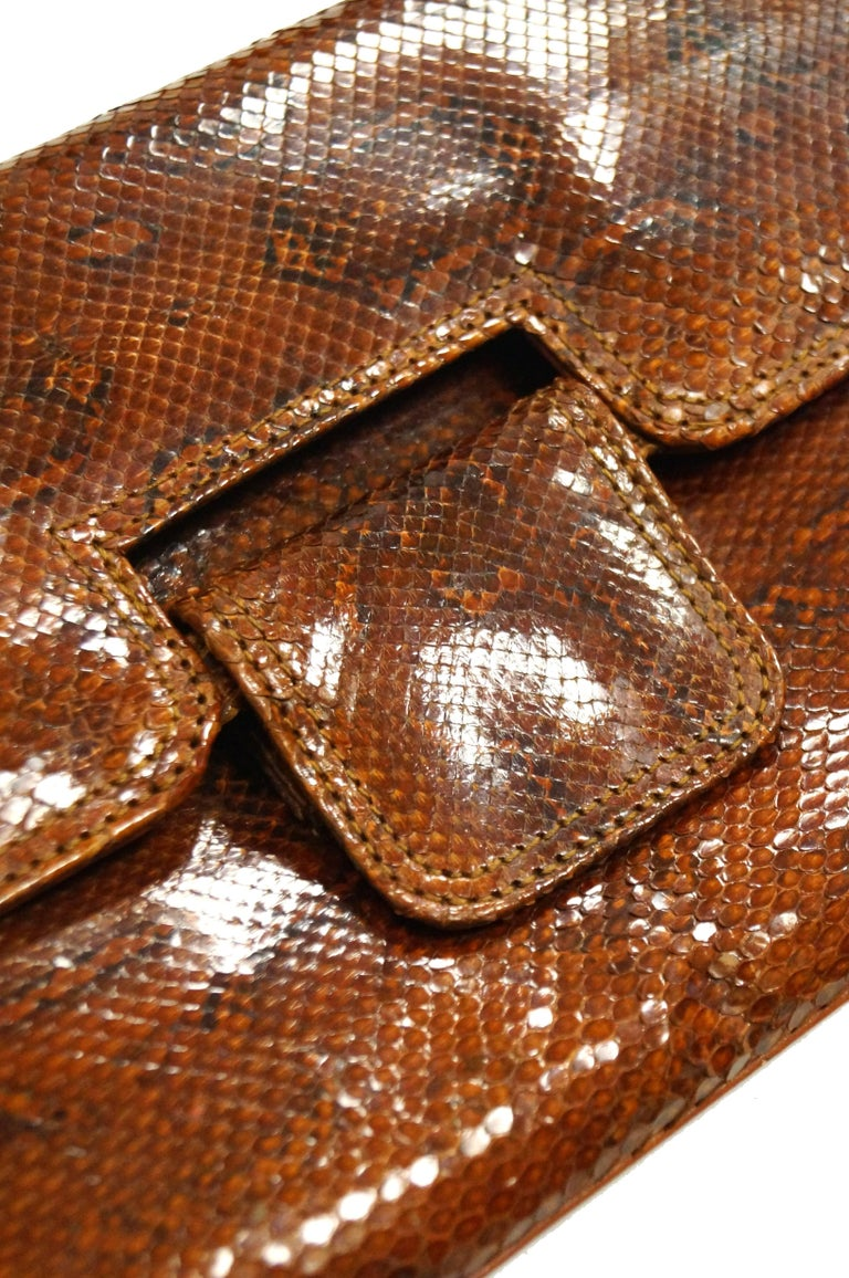 Gorgeous ochre - tone Argentine python snakeskin clutch by Rosenfeld! The clutch is rectangular, with clean lines and a glossy finish, as well as a fold-over closure. The interior is lined in tan leather, has a pocket, and features the Rosenfeld
