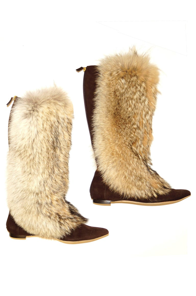 Warm, wild, and ever so wearable! These Oscar de la Renta russet brown suede boots have a lush, fluffy fur exterior covering the boot from below the knee to just past the bridge of the foot. The fur has a cream-colored base with warm grey and white