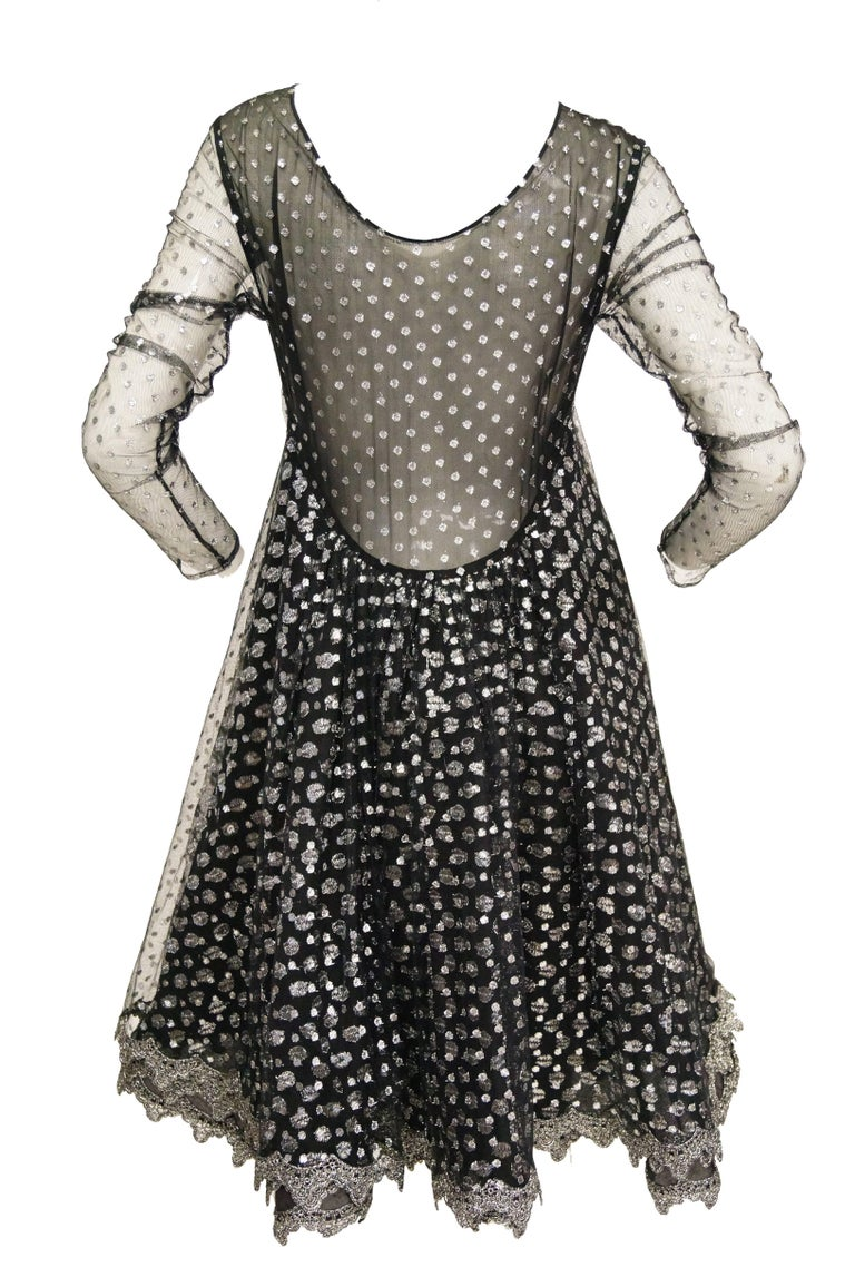 "Geoffrey Beene channels the 1960s in this ""MR. Beene"" made in the early 1990s.  The dress has oh such wonderful movement and shine!   Two layeers of silver metallic polka dotted tulle, one smaller dots than the other. Sheer sleeves. Attached sewn in"