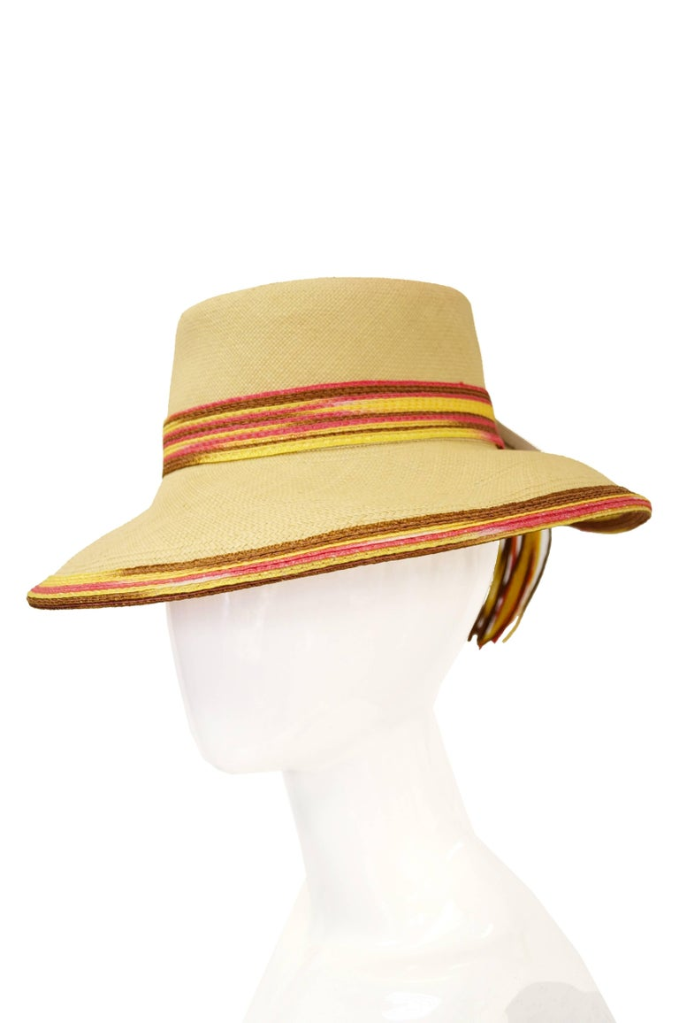 Playful and timeless sun hat by Yves Saint Laurent is perfect for your a weekend at the beach or just keeping your face out of the sun.    The woven hat features a sandy yellow upper with colorful pink and brown edges and trim. The back of the hat