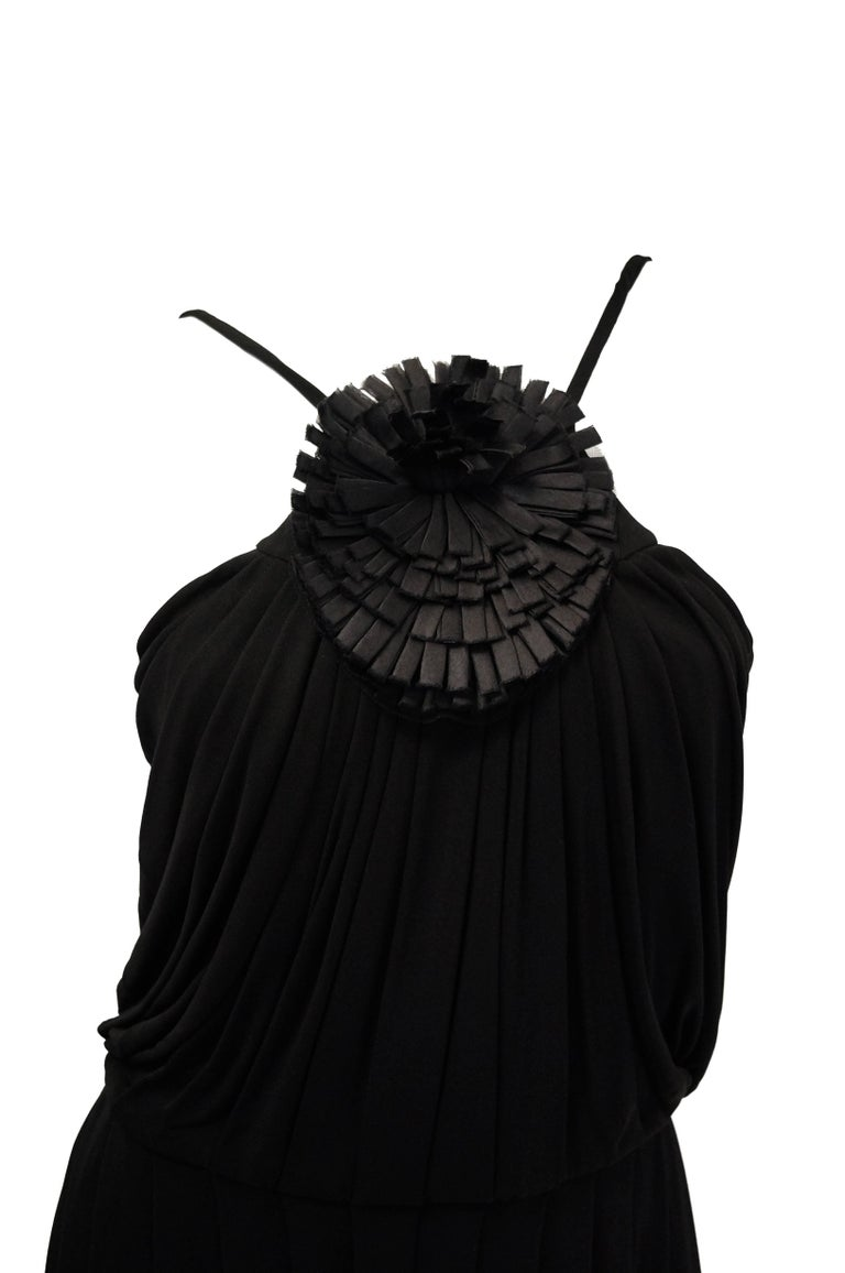 Classic black knit maxi evening dress by Fendi! The dress has a halter neckline accented by a brilliant oversized black flower composed of pleated ribbons arranged in an asymmetric pompom - like tuft! The elegant draped dress features a blouson -