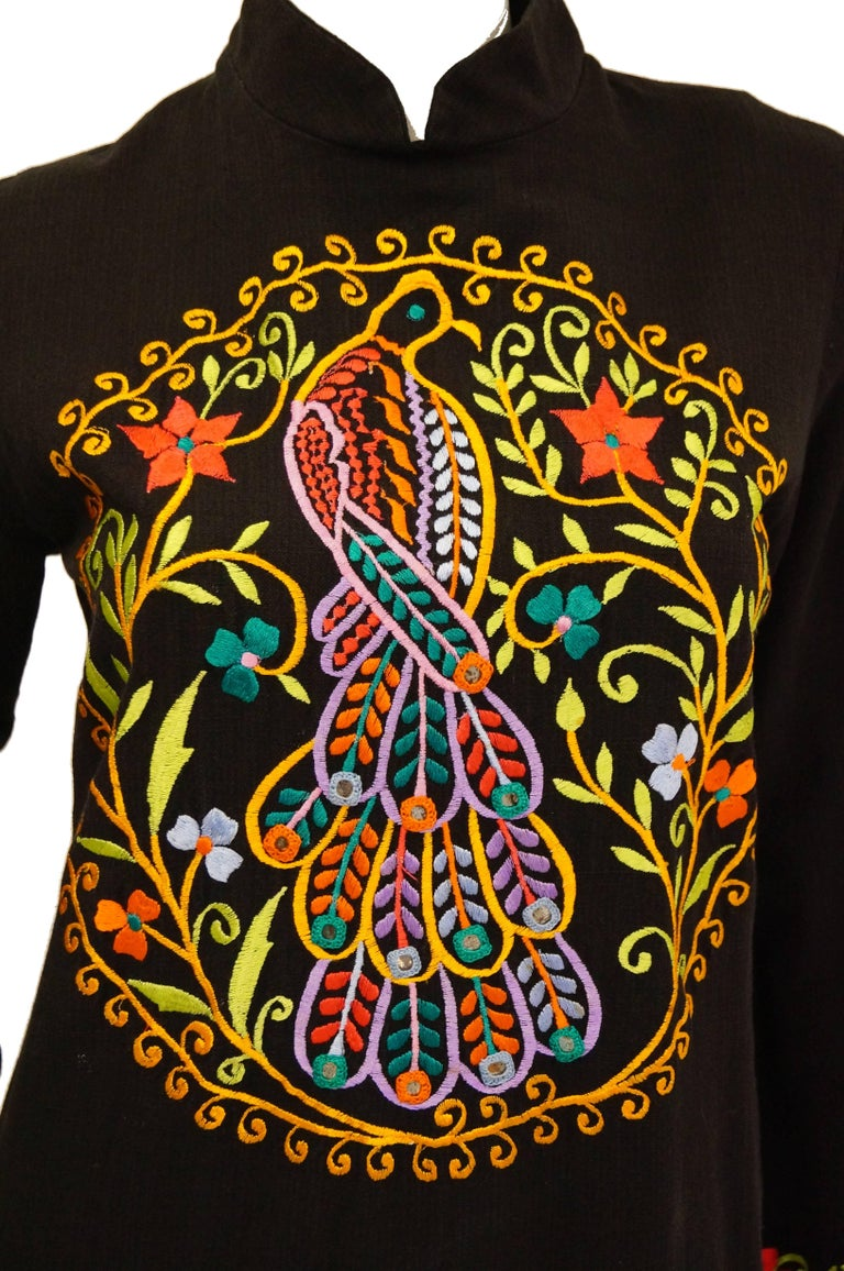 Fabulous colorful peacock embroidered caftan / kaftan by Ramona Rull! The 100% cotton caftan features a high mandarin collar, long sleeves with a slight flare, and has knee-length slits on both legs. The dress is embroidered in a multitude of colors