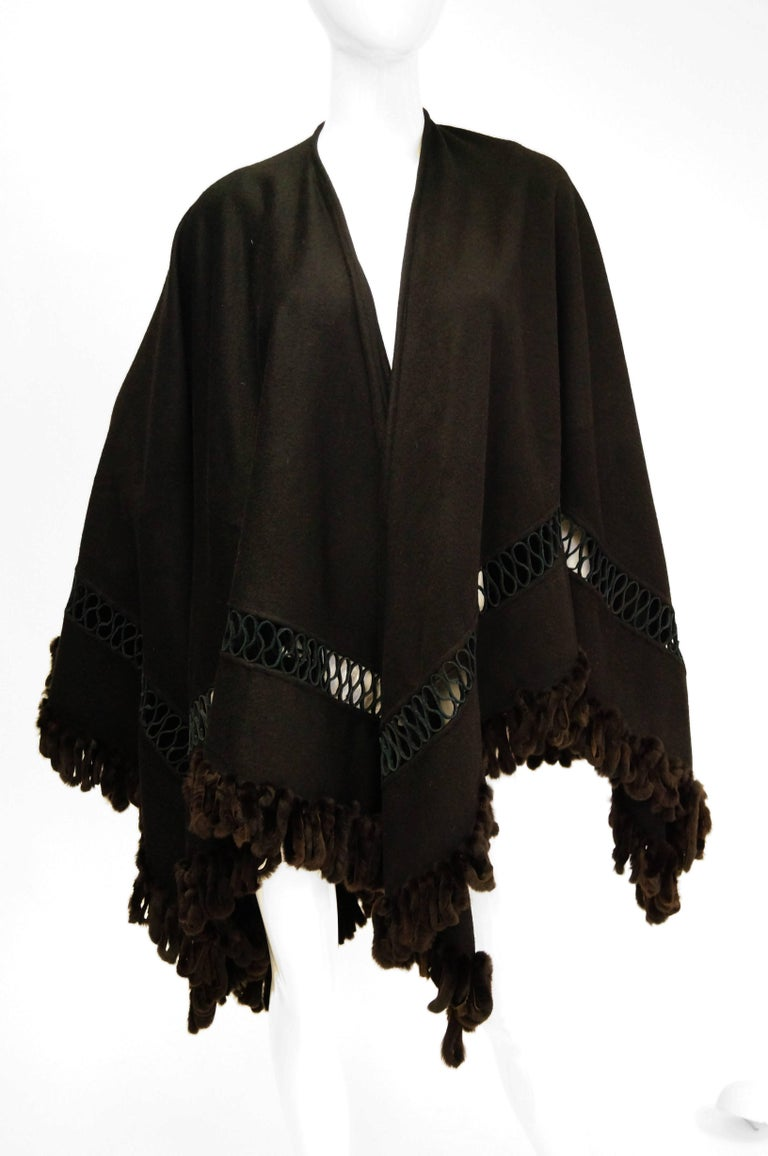 Fabulous intricate wool and fur shawl by Adrienne Landau. This solid black shawl by Adrienne Landau is diamond cut with a straight center line up to the neck. The shawl is made of a medium-weight wool that is weighed down with a fox fur tassel trim.