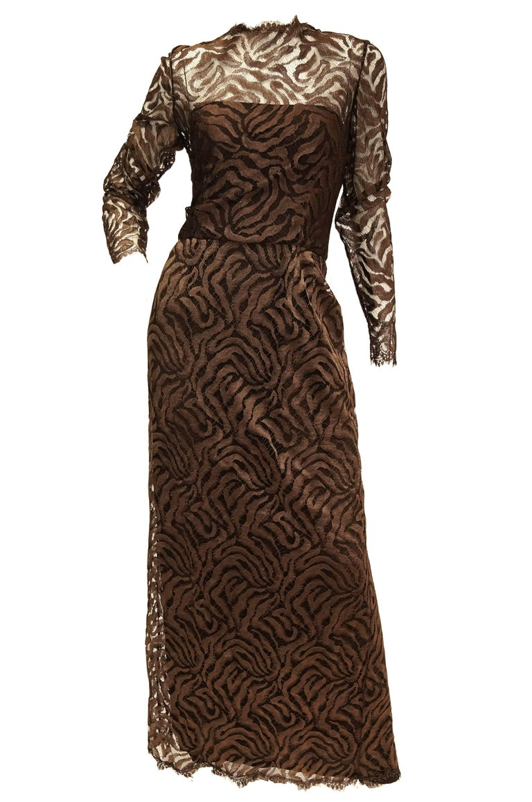 Elegant floor length maxi dress by Stanley Platos Martin Ross. The Dress features long sleeves and a slip - like layering dress. The bottom layer of the dress is brown, floor length, and sleeveless, with a straight - across neckline. The top layer