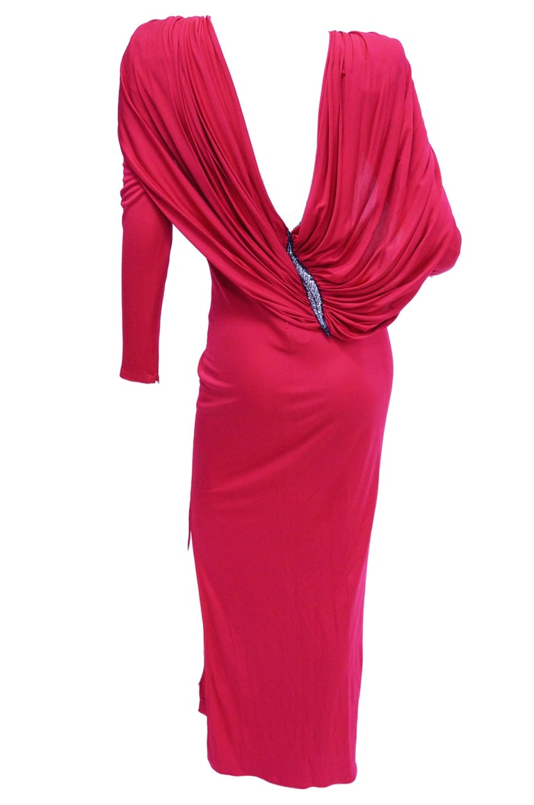 Amazing hot pink maxi length evening dress by Valentino with plunging back AND cape detail. The silk dress has long sleeves and jewel neckline, as well as a slit on the left leg that reaches just below the knee. The most prominent detail of the