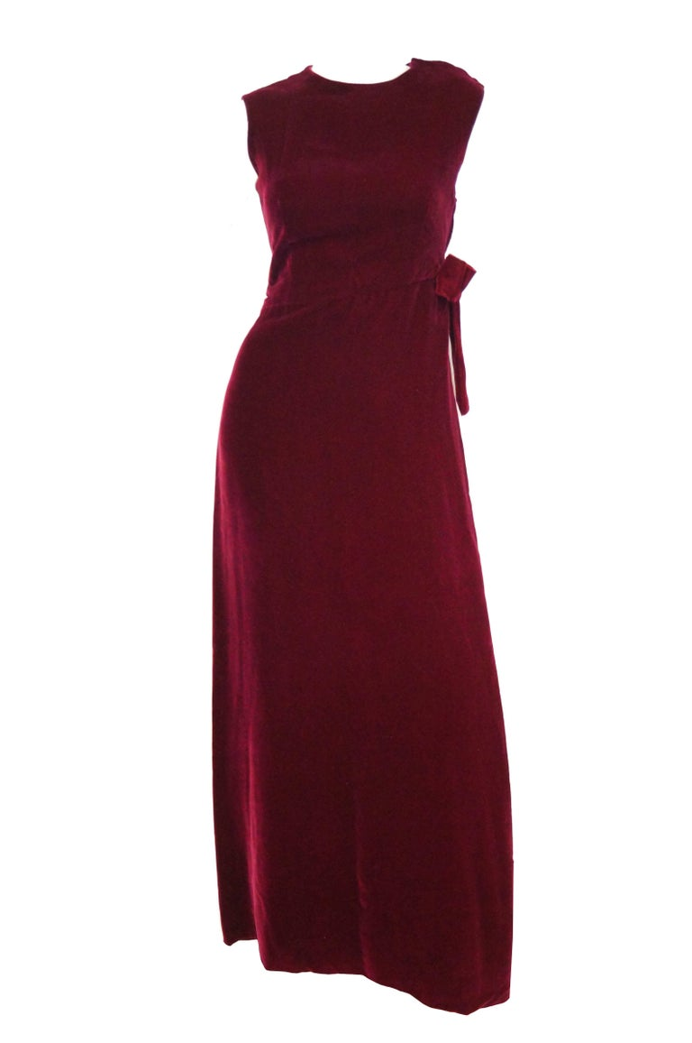Striking dark burgundy velvet evening dress by Sarmi. The dress is sleeveless, has a high jewel neckline, and a high, left-to-right sloping waistline. The highest tip of the waistline is marked by a large velvet bow. The dress has a fabulous slit in