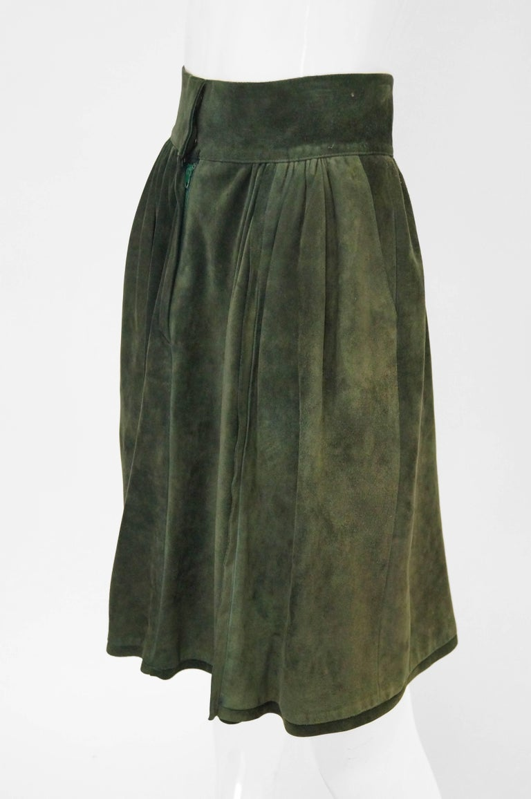 Green suede symmetrically pleated Mario Valentino skirt. Skirt is knee length, with a wide waist band, and zipper closure. Has pockets hidden in the pleats! Made in Italy.