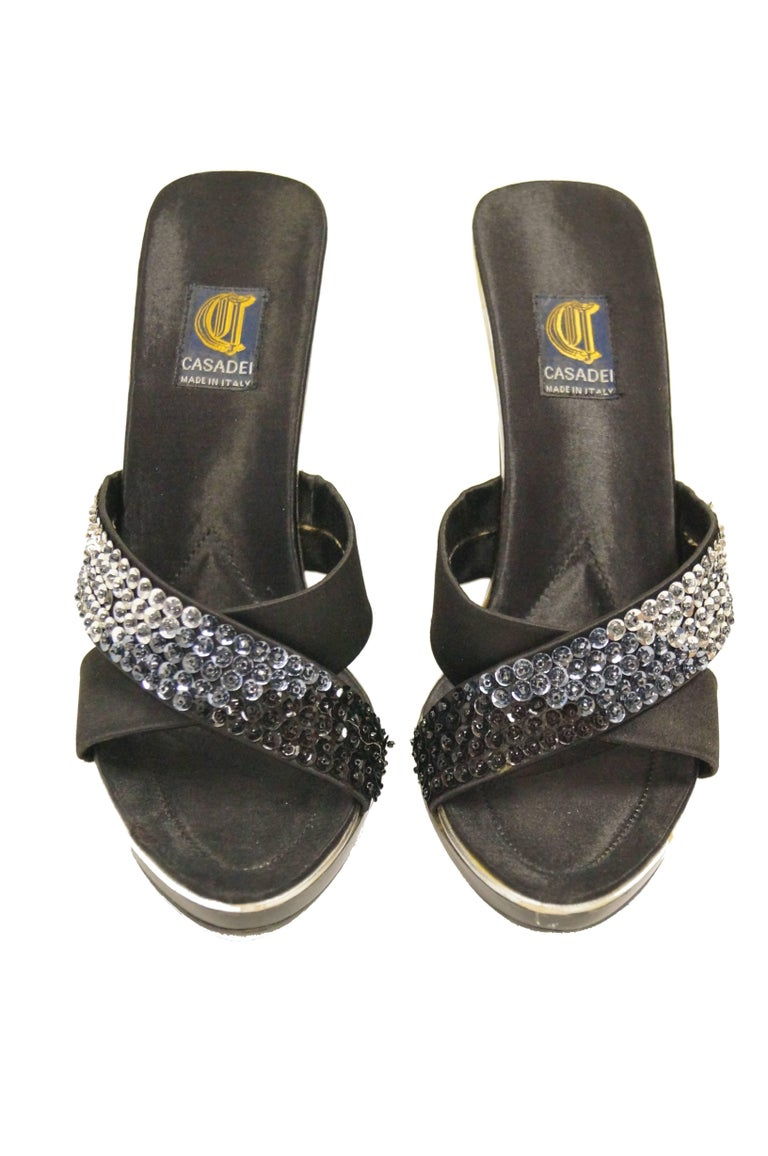 Criss-cross open back sandals by Casadei! The sandals feature two black - to silver ombre sequin satin straps that cross over to form an