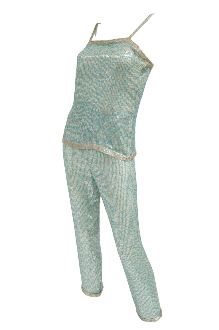 Incredible and outrageous three piece blue beaded and sequin ensemble by Naeem Khan for Riazee! The ensemble consists of a pair of fully sequined blue straight - leg pants with elastic waist, a sequin top with white tube beaded spaghetti straps, and