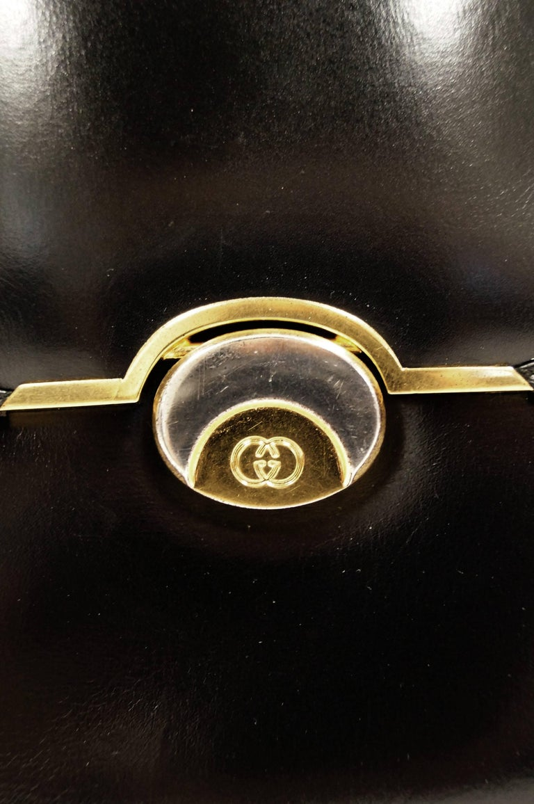 Wonderful glossy black leather top handle bag by Gucci. The handbag is composed of a structured rectangular body with curved edges and expanding accordion sides, a flap opening with gold and silver tone engraved half moon closure clasp, and a firm