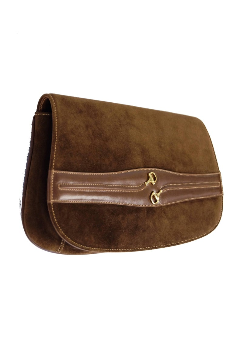Elegant brown suede clutch by Gucci. The clutch has a rectangular trapezoidal shape with rounded edges (rather like a saddle bag) harkens back to Gucci's foundation as an equestrian leather atelier. The clutch features a strip of leather across the