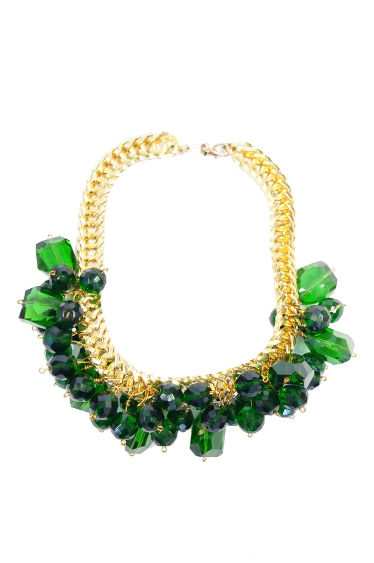 Striking bottle green glass on gold chain necklace by Accessocraft. The necklace is composed of numerous overlapping cut glass beads of varying sized and shapes, clustered together and affixed to a gold tone curb chain. The necklace is of a