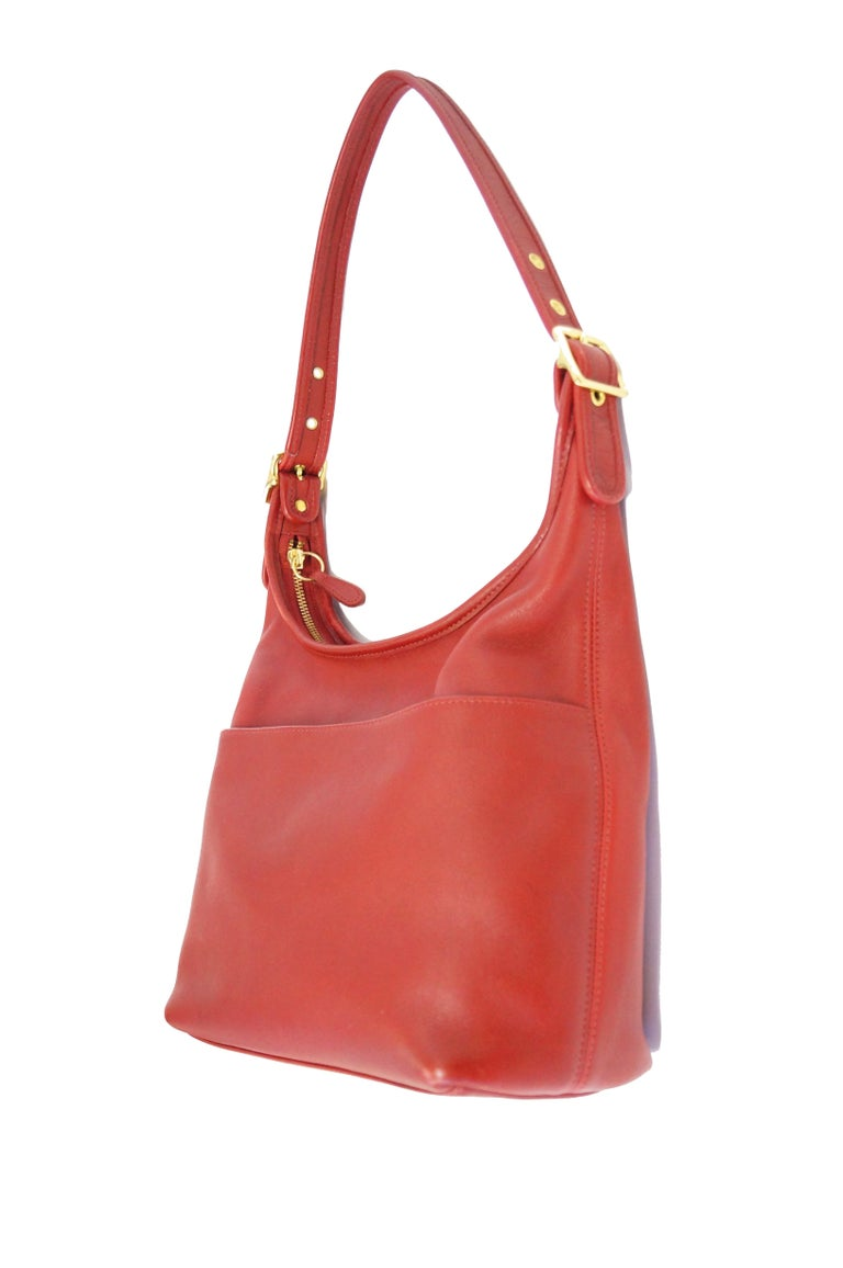 Fabulous vintage Coach bag by Cashin! This tomato red shoulder bag features a single deep pocket on the exterior of the handbag, an adjustable shoulder strap with buckle, and a zipper - top closure. The interior of the handbag has a zippered pocket,