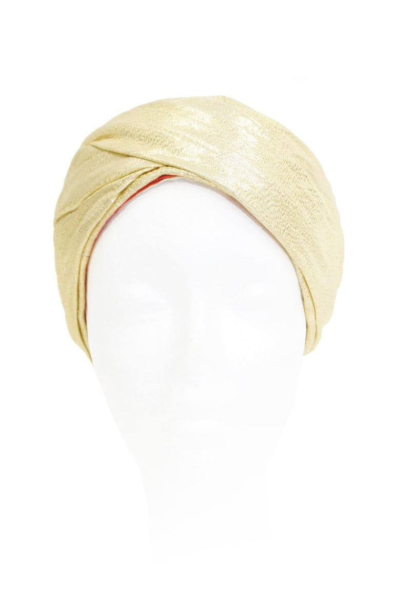 Extremely Rare Gold fabric pleated turban by Avant Garde designer Pierre Cardin.  Extremely well designed and constructed.  Turban can be worn high on the head or pulled down covering the crown. The turban is lined with red fabric and gross grain