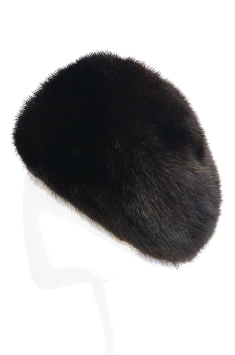 Beautiful dark espresso brown hat by Christian Dior Chapeaux. This mink hat has a rounded crown with gently sloping sides, long enough to keep the wearer's ears warm! Lined and features a grosgrain ribbon. The hat was sold at Marshall Fields'