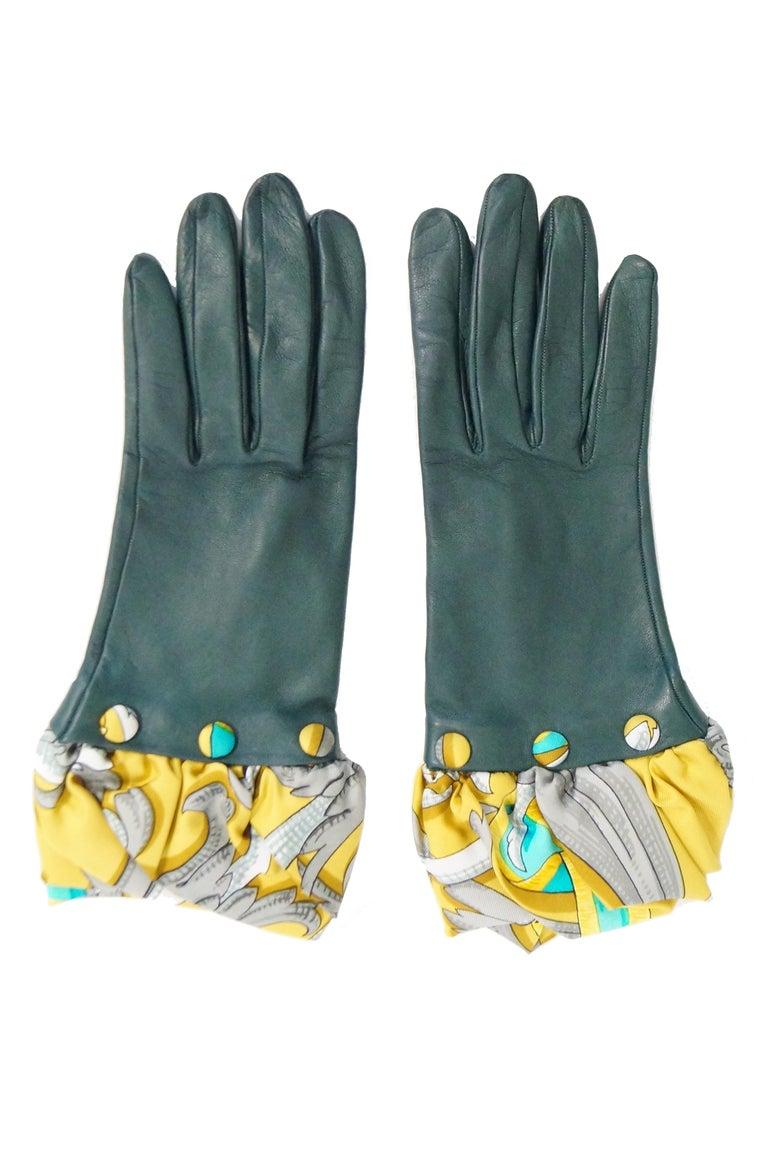 Gorgeous viridian green leather gloves by Hermes. The gloves are composed of a buttery soft calfskin leather, with suede interior, and a striking optional cuff! The silk scarf cuff features a gold background with aqua blue and pewter grey accents in