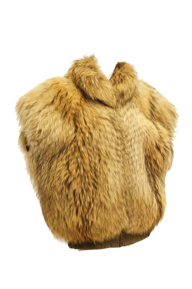 Yes, this is a vest. THE VEST!   Amazing golden brown fox fur and nutria coat with cinched suede waist and zip closure. The vest has a high collar, batwing sleeves, and so much panache.  Personalized monogram can be removed by your local furrier.