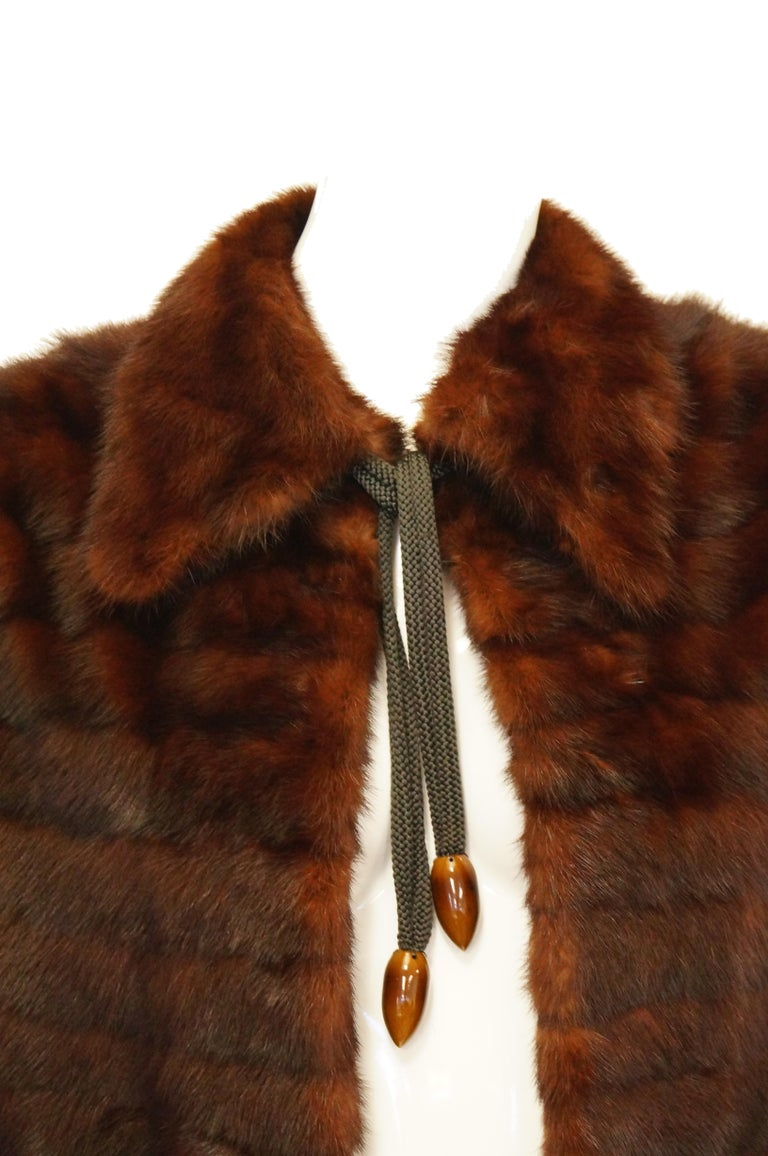 Wonderful deep chocolate brown feathered Mink cape by Arnold Liebes. The cape is hip length, with a straight collar, and fastens at the neck with a grosgrain rope with AMAZING swirling polished bakelite acorn - like aglets. The cape is lined in