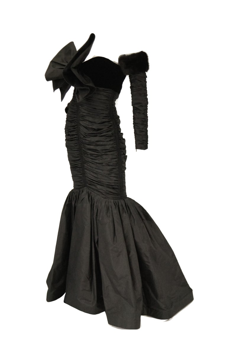 Amazing fit and flair evening gown by Nina Ricci. The black dress is maxi length with a strapless bodice, and curve - hugging silhouette with ruching detail that runs from just below the velvet bust down to the knee. The front of the dress features