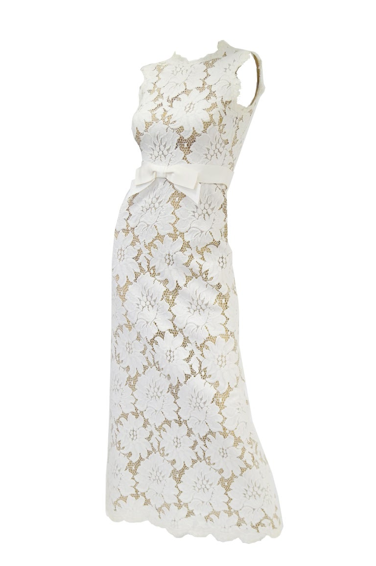 Absolutely gorgeous white floral lace sleeveless dress has grosgrain waist line and bow. Scalloped hem line. Lined with a tan cotton lawn fabric. Zips in back.