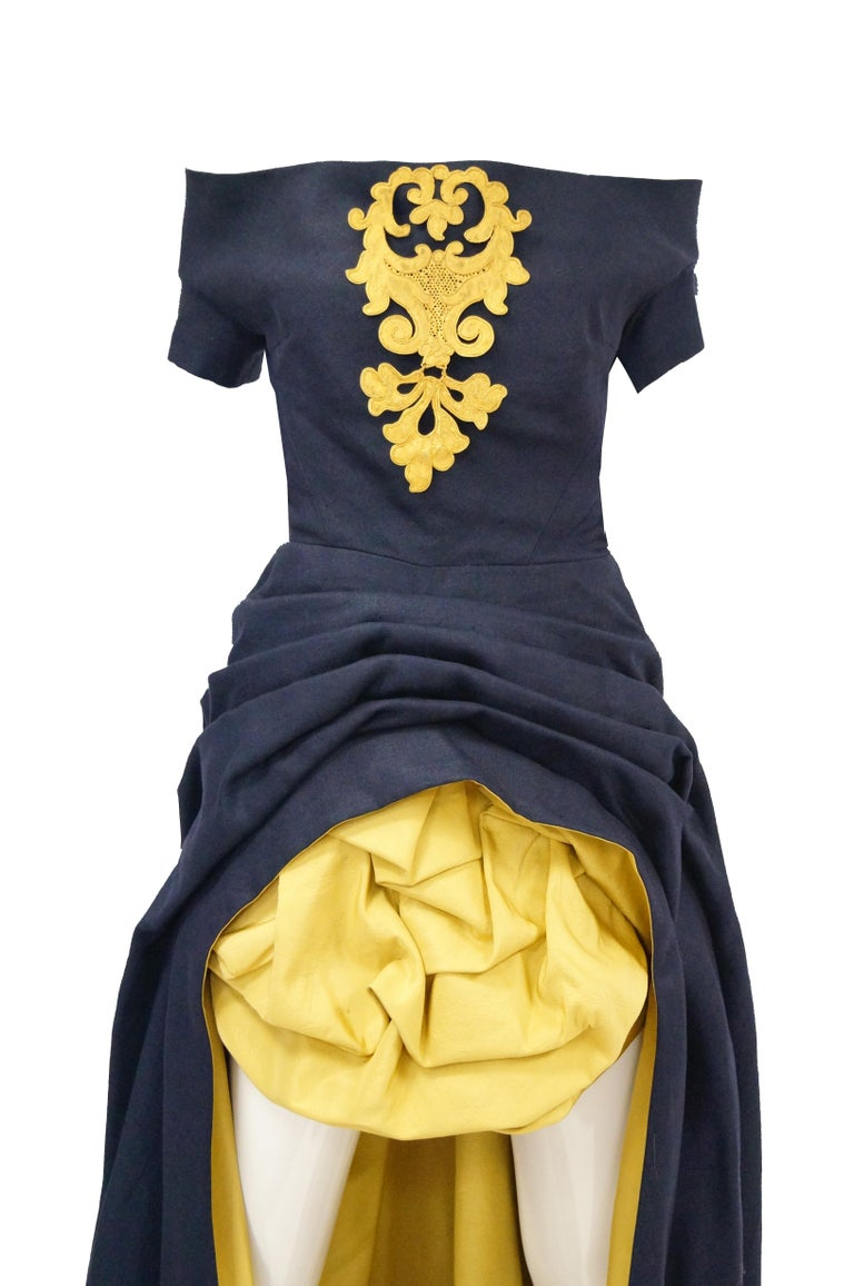 Museum worthy and quite wearable 1991 Couture Navy and Gold gown. Dress contains inner corset with boning and zipper and an inner belt. Detachable large gilt gold breast brooch based on 17th Century strapwork design. Gathered at hips and under mini