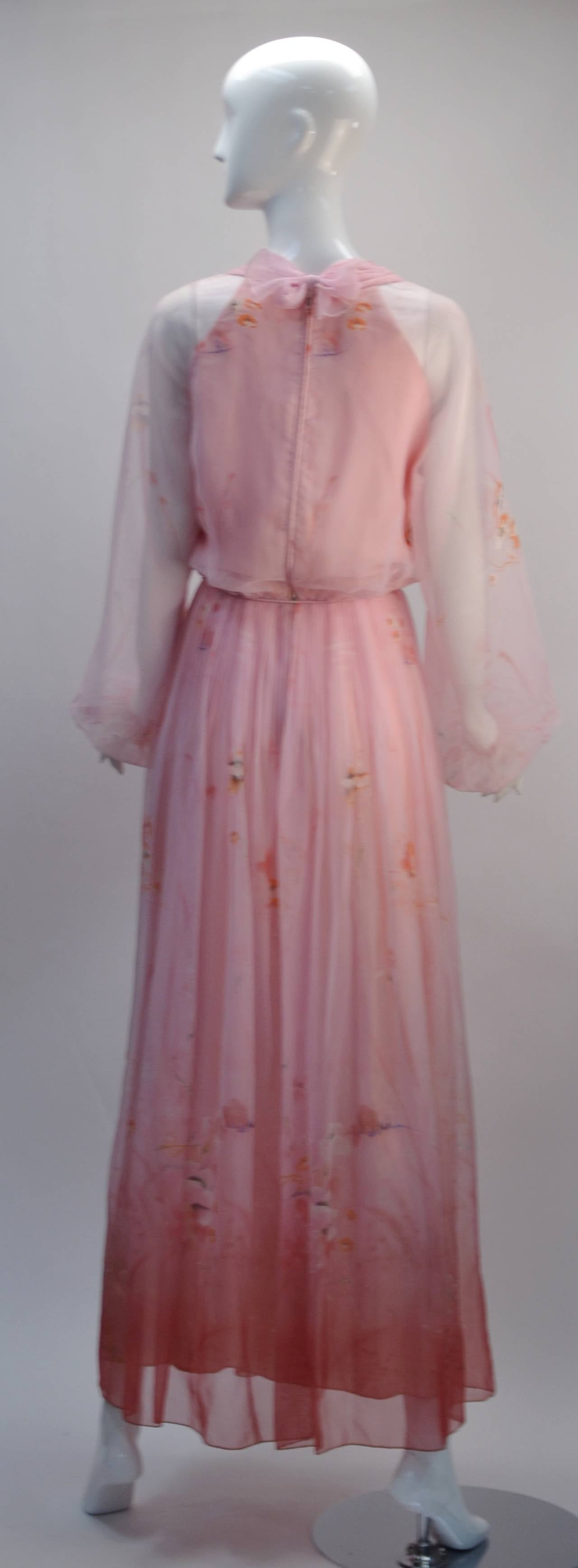 Sheer light pink fabric is pleated at the waist line as color intensifies at the hem creating an ombre effect. Sweet tie at waist. Layers of fabric create a halter look under the sheer pink fabric. Perfectly long sleeves are sheer and cool. Tiny