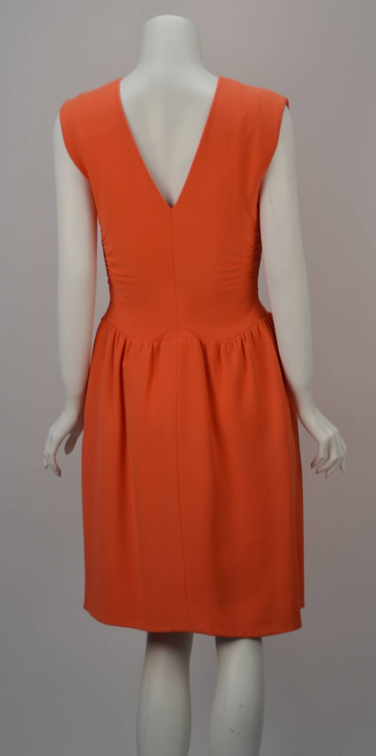 Norman Norell knee length coral dress. Ruching at sides and a gathered waistline with center accent makes this dress very special. Coral is a wonderful color for spring and this vintage stunner looks fresh. Rock it with some gold heels and
