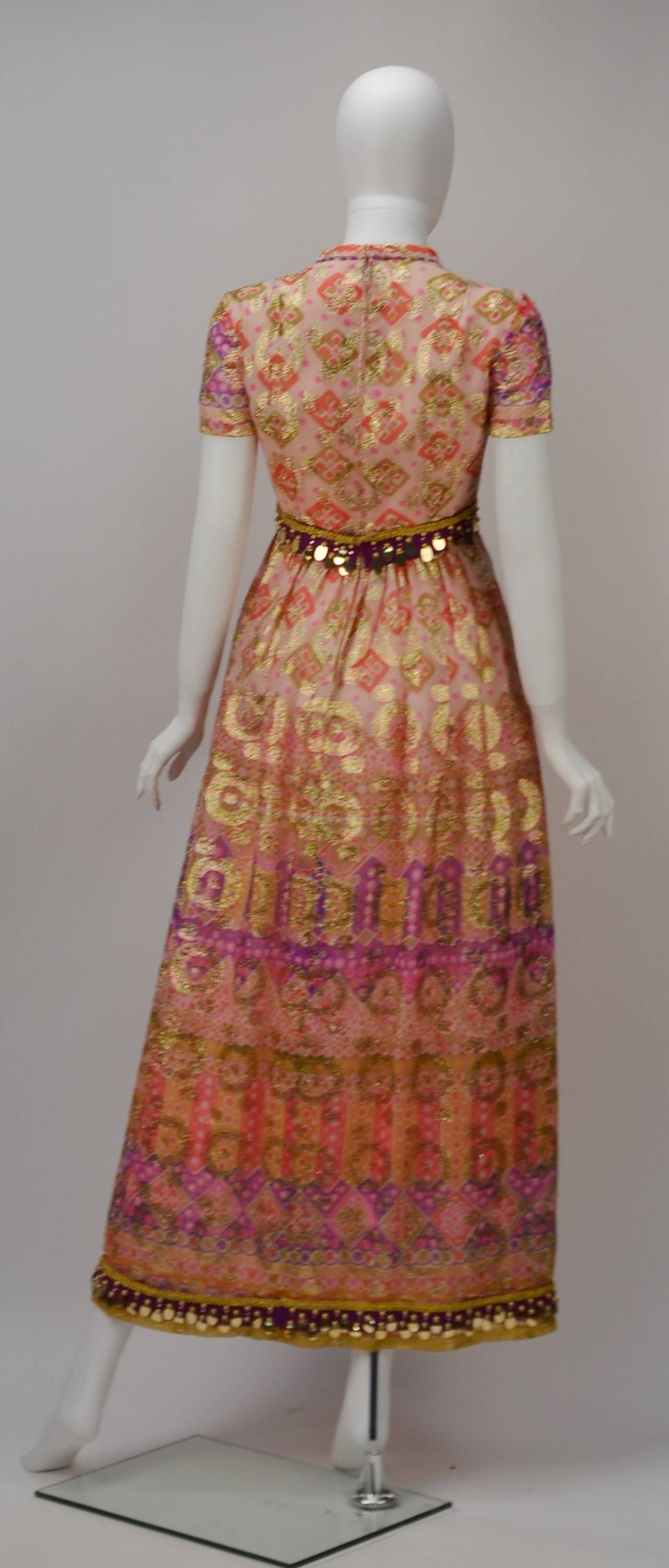 Teal Gino Traina and Malcolm Charles Starr loved exquisite fabrics. Evidence can be found in this pink, purple and gold print dress. Empire waist and a mandarin collar that opens in a deep V. Gold dot sequins dangle at the waist and hem. Fitted