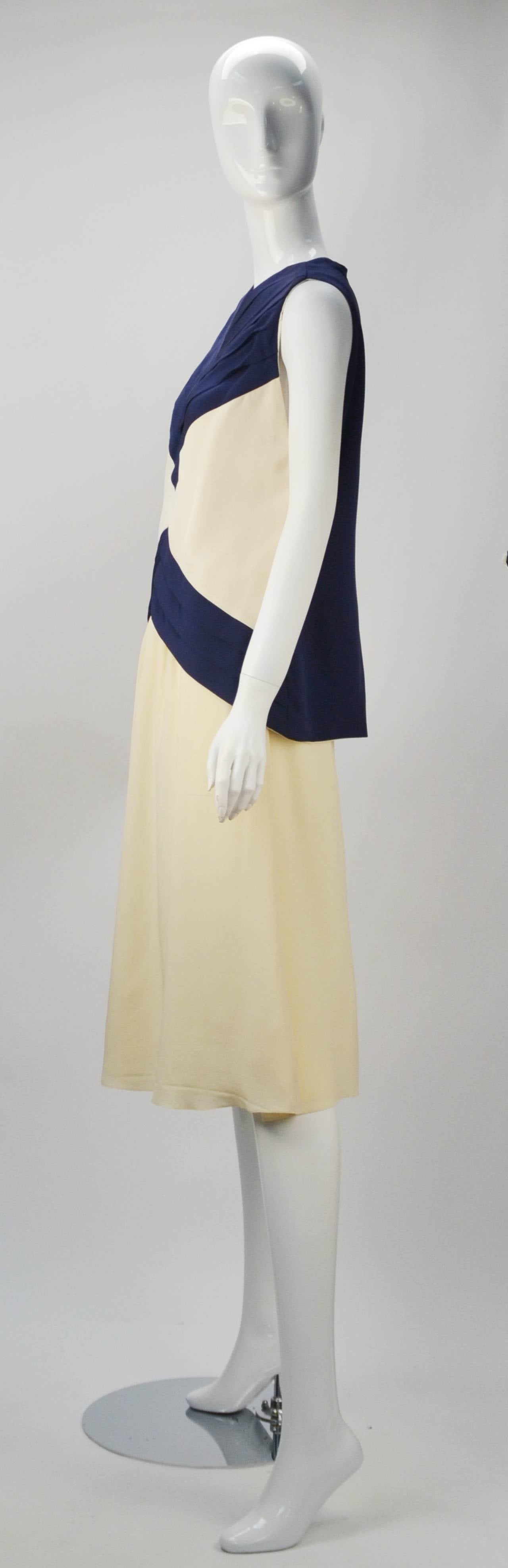 Grab your skipper and go yachting in style with Oscar de la Renta's nautical Art Deco look, two piece set. Navy blue silk pleated details on front bodice.  Back bodice is solid navy. Raglan styled deep arm holes. Long zipper at back. Flowing cream