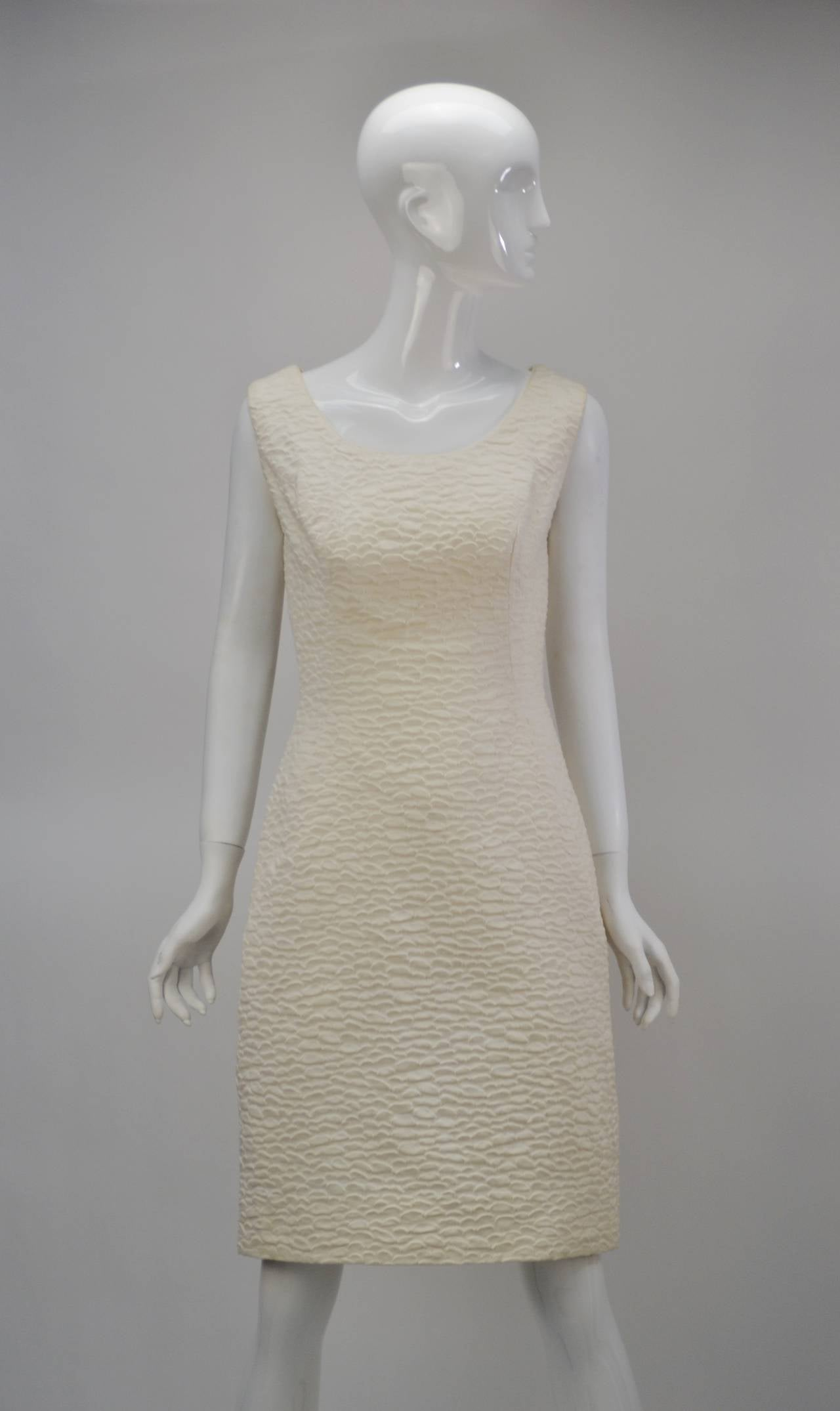 Stunning Mr. Blackwell ivory cocktail dress and cape. Both garments are lined in silk, with a wavy, textured fabric as the focus. The sleeveless dress features a dainty scoop neck and a zippered back closure. It has princess seaming in the front and