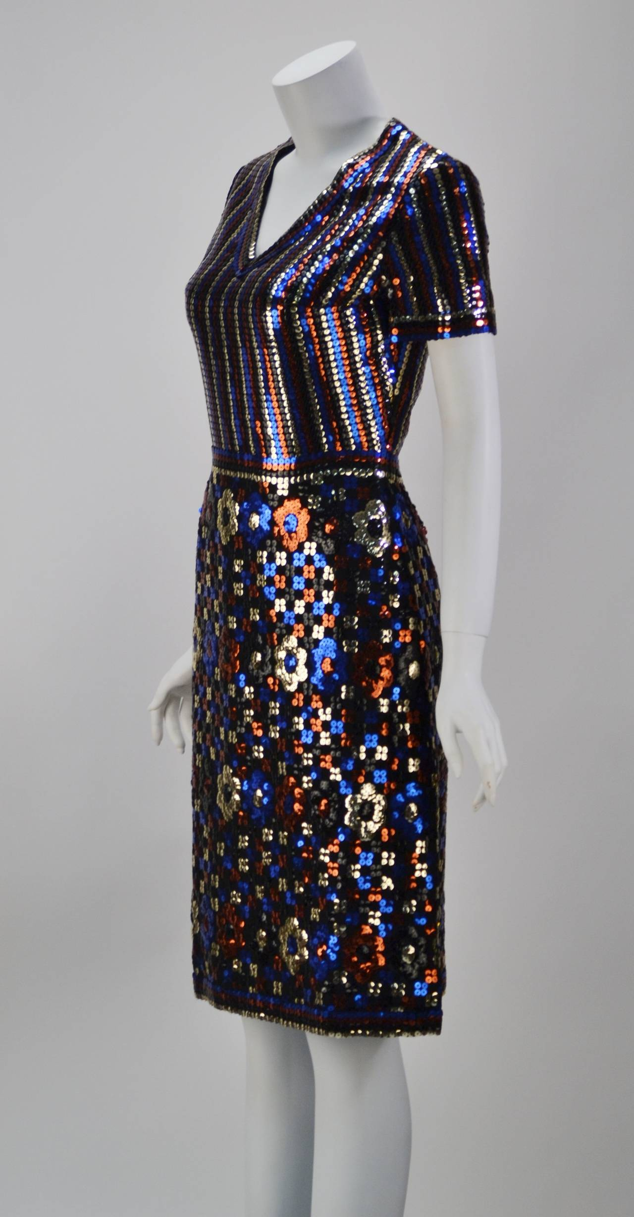 Stunning 1960's short sleeve, v-neck black silk with red, blue, black and silver sequins dress by Trevise, Paris. The top of the dress has the sequins going in vertical rows, while the skirt has the them in floral designs. It has a zippered back