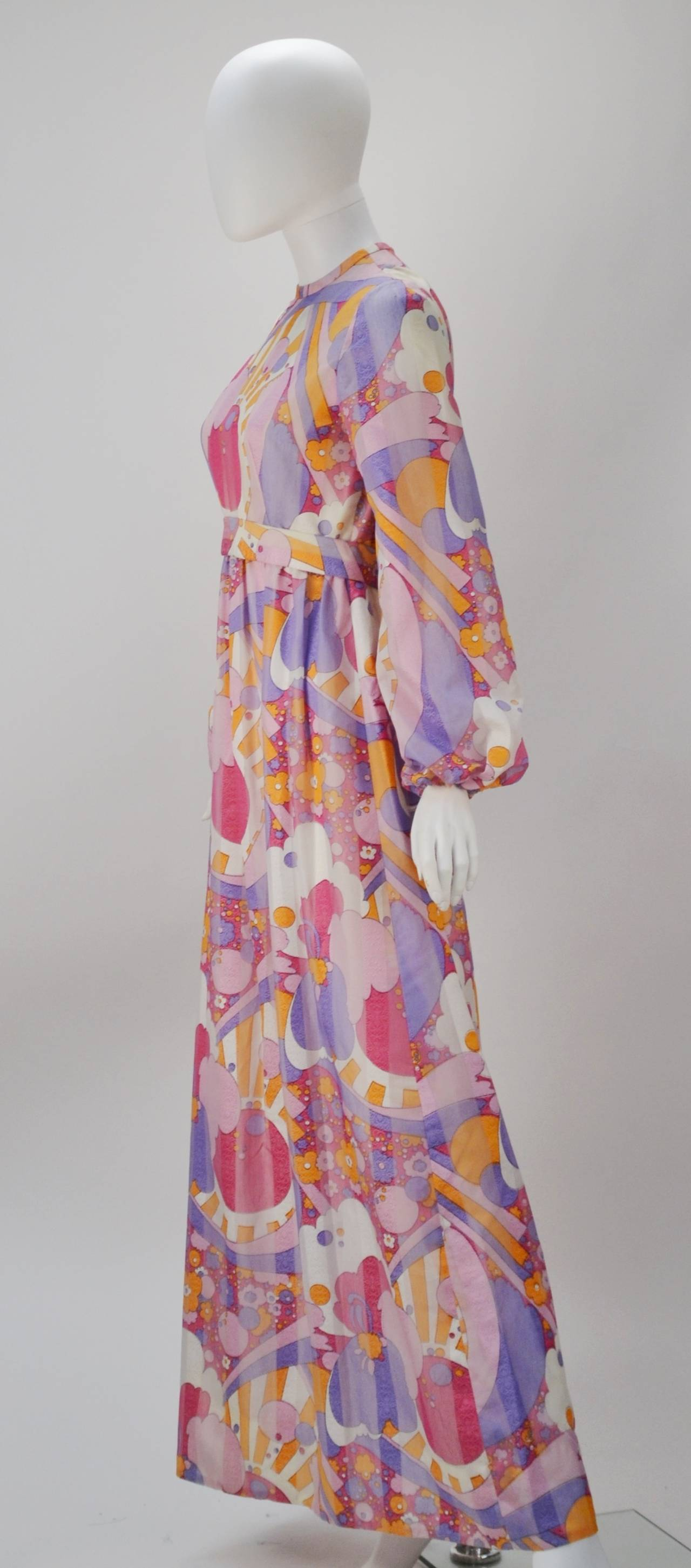 1960's Rodrigues vibrant multi-color print dress with blouson sleeves. This lightweight dress has an silk embroidered stripe throughout this perfectly whimsical dress. The dress also features a back zippered closure with a waistband that fastens