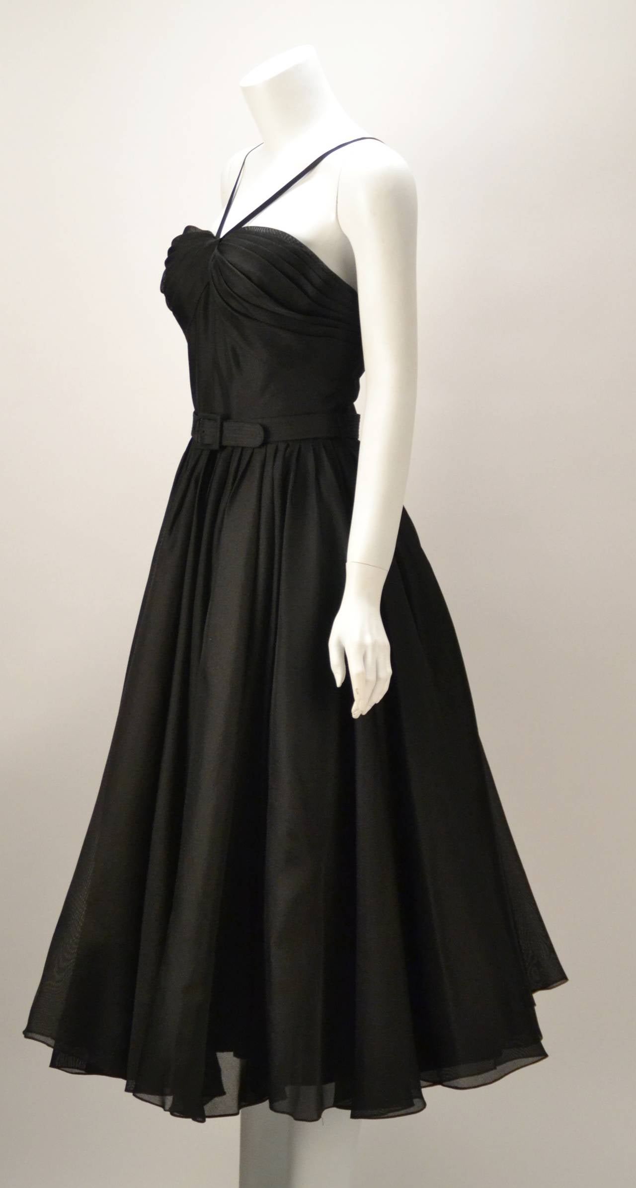 Extremely beautiful rare dress created by Traina-Norell in 1955.    The halter day or evening dress is made of black taffeta and boasts a sheer overlay halter attached to a circle skirt.  Fine leno weave fabric, pronounced horizontal gathering