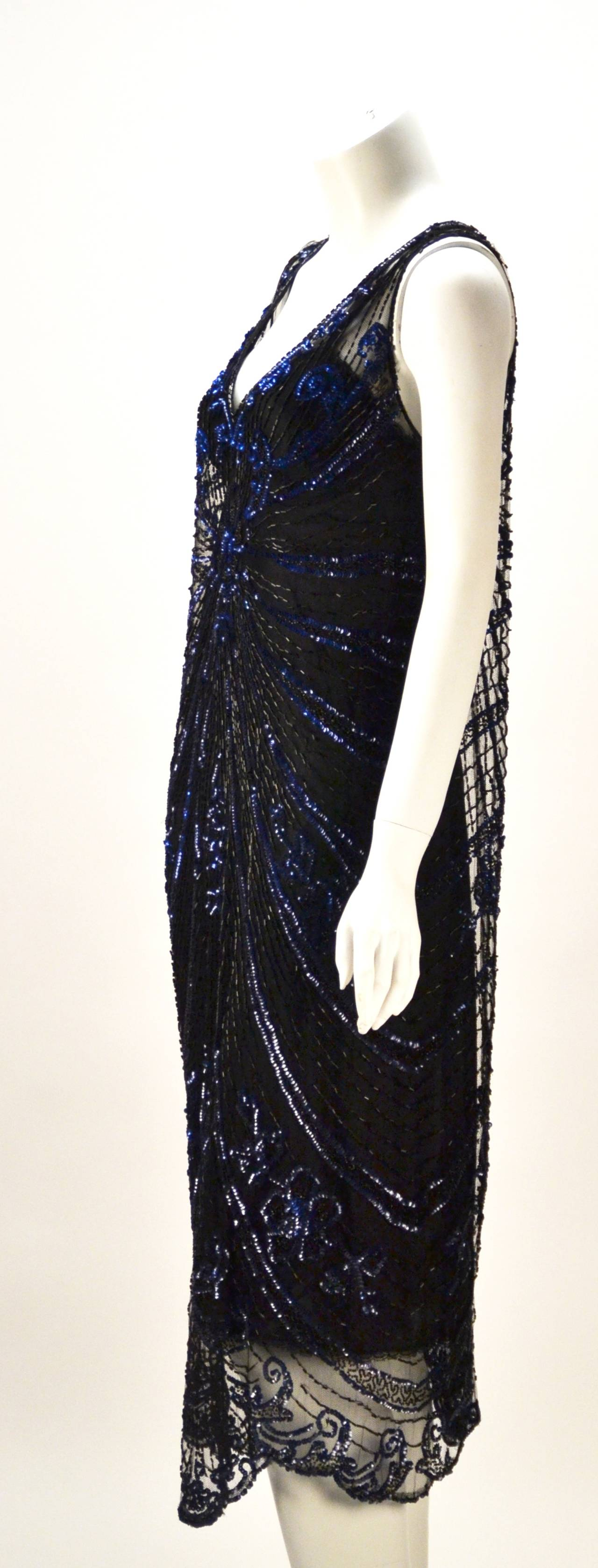 Awesome 1920's net sleeveless black and blue sequin and bugle beaded flapper dress! This dress marks the essence of beauty and luxury during the Art Deco era with exquisite beading and sequins and sculpted skirt hem. The beading and sequins form a