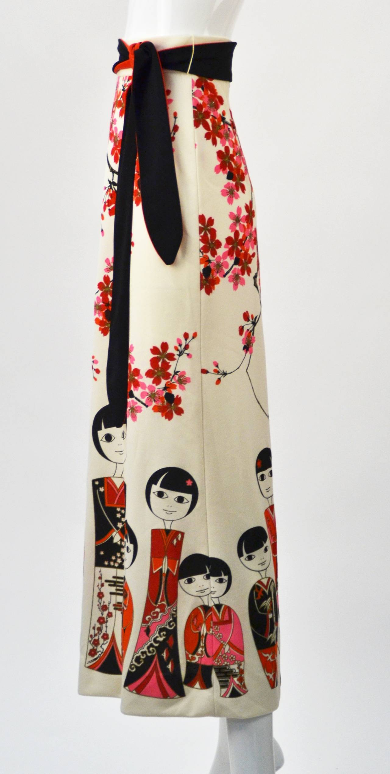 Fantastic 1960's print Miss Shaheen Japanese Kokeshi Doll border print maxi skirt with obi belt. Brilliant print by the master of Hawaiian print design, Alfred Shaheen.  The colors are vibrant and pop against the skirt's white background.  Shaheen's
